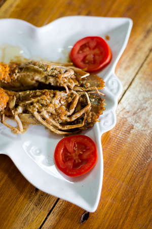 Flathead lobster fried with garlic served with tomato slices in local port restaurant. Traditional thai seafood cuisine made of fresh ingredients. Stock Photo