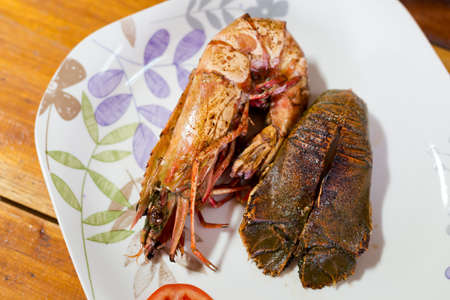 Flathead lobster fried with garlic and grilled giant prawn served with tomato slices in local port restaurant. Traditional thai seafood cuisine made of fresh ingredients. Stock Photo