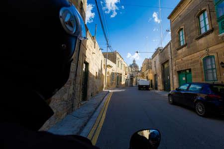 Sandstone cityscape of Gozo island taken during motorbike trip. Historical architecture of Malta.