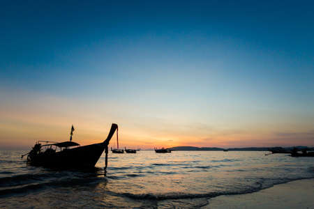 Beautiful sunset on tropical beach Ao Nang (Ao Phra Nang), Thailand. Landscape with longtail boats while sun is going down