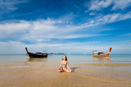 Tropical summer yoga session on beautiful Charlie Haad Farang beach, Koh Mook island in Thailand. Meditation - jnana mudra in lotus pose. Healthy lifestyle concept  Stock Photo