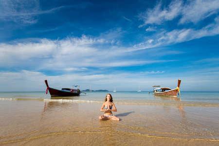 Tropical summer yoga session on beautiful Charlie Haad Farang beach, Koh Mook island in Thailand. Meditation - namaste in lotus pose - padma asana  Stock Photo