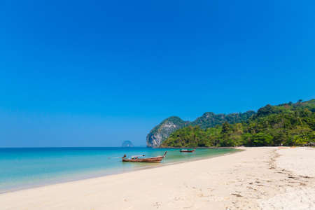 Longtail boat on tropical Koh Mook island in Thailand. Landscape taken on Charlie beach, Haad Sai Yao - Haad Farang with blue sky and white sand.