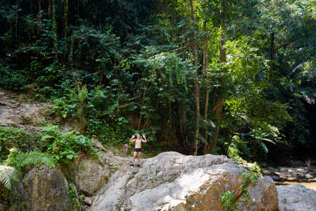 Young tourist on Huai To waterfall in Khao Phanom Bencha Krabi southern Thailand. Landscape in real rainforest taken in beautiful reserve in south east Asia. Stock Photo