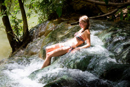 Young woman tourist taking healthy bath in Krabi hot springs waterfall in southern Thailand. Tourism in beautiful south east Asia. Stock Photo