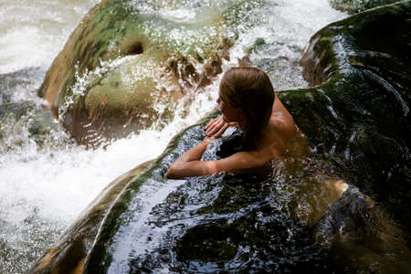 Young woman tourist taking healthy bath in Krabi hot springs waterfall in southern Thailand. Tourism in beautiful south east Asia. Foto de archivo