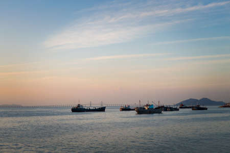 Landscape with Penang bridge connecting land and island on Penang island in Malaysia. Beautiful seascape and harbor during surise taken from ferry. Stock Photo