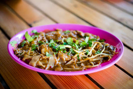 Fresh prepared malaysian Char Kuey teow noodles in local restaurant on Pangkor island. Traditional asian cuisine made of fresh ingredients.
