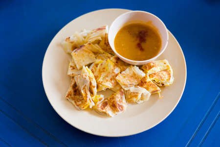 Fresh prepared Malaysian roti telur with egg served with lentil dahl in local restaurant on Langkawi island. Traditional asian cuisine made of fresh ingredients. Archivio Fotografico - 114824931