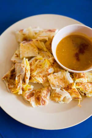 Fresh prepared Malaysian roti telur with egg served with lentil dahl in local restaurant on Langkawi island. Traditional asian cuisine made of fresh ingredients.