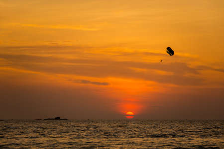 Watersport parachute on Pantai Cenang beach on tropical Langkawi island in Malaysia. Beautiful nature of south east asia during colorful sunset. Stock Photo