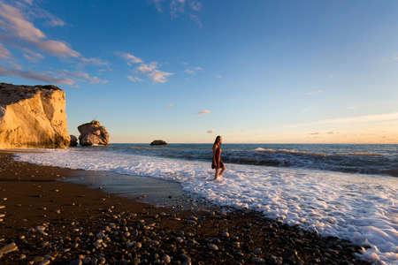 Young caucasian woman tourist on beautiful Aphrodite's rock on stone beach during susnet. Landscape taken on Cyprus island. 免版税图像
