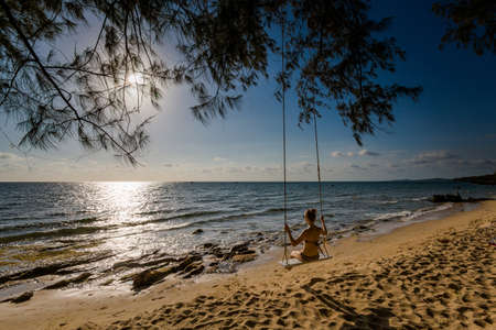 Young sexi woman on swing on tropical island Phu Quoc in Vietnam. Tourist on Ong Lang, Cua Can beach during hot sunny day.