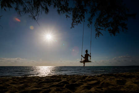 Siluette of woman on swing on tropical island Phu Quoc in Vietnam. Tourist on Ong Lang, Cua Can beach during hot sunny day. Foto de archivo