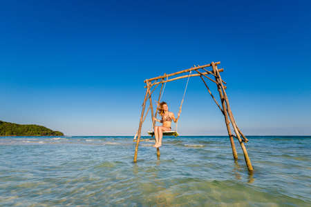 Young sexi woman on swing on tropical island Phu Quoc in Vietnam. Tourist on Sao beach during hot sunny day.