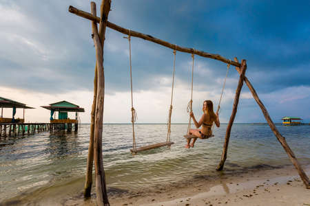 Young sexi woman on swing on tropical island Phu Quoc in Vietnam. Tourist on Starfish beach, Rach Vem during hot sunny day.