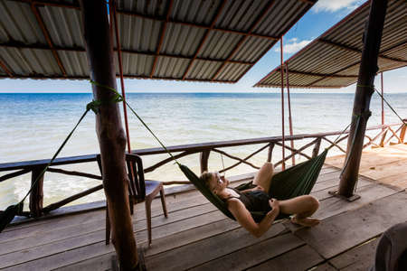 Young goodlooking man lying in a hammock in local seafood restaurant in  fishermans village Ham Ninh, tropical Phu Quoc island (Bai Thom area) in Vietnam. Holidays chillout