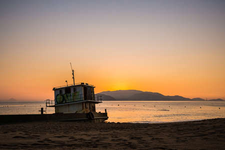 Old boat on a beach during beautiful golden sunrise in Nha Trang, Khanh Hoa province in Vietnam.