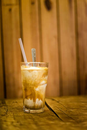Glass of traditional vietnamese coconut ice coffee with a spoon and straw. Picture of popular cafe of Vietnam in Da Lat