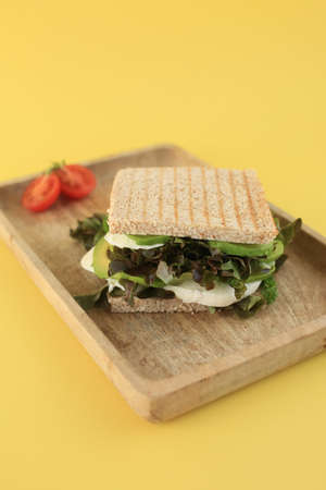 Tasty green vegan sandwich with salad. parsley, avocado, mozzarella and tomato, covered with toasted bread on eco wooden plate on yellow background.