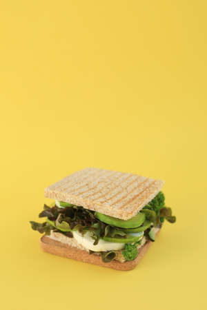 A tasty green vegan sandwich with avocado. lettuce, parsley, mozzarella on toasted bread placed on yellow background. Stok Fotoğraf