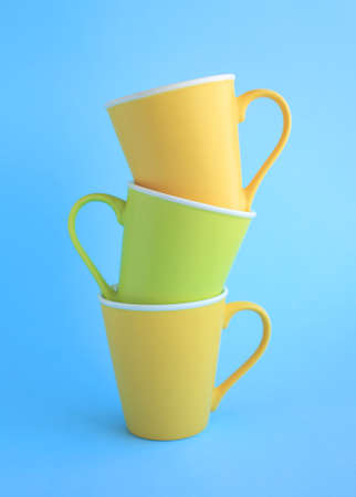 Three colorful yellow and light green ceramic cups on light blue background.