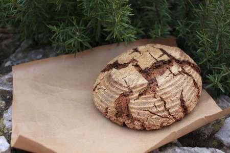 Bio whole grain homemade bread made on sour dough laying on kraft paper on stone curb near rosemary, shot in rustic style.