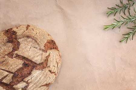 Bio round whole grain homemade bread made on sour dough laying on kraft paper near rosemary, shot in rustic style.