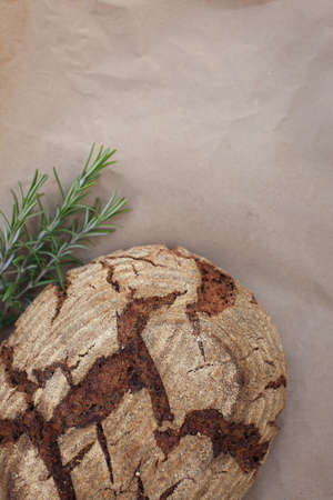 Bio whole grain homemade bread made on sour dough laying on kraft paper near rosemary, shot in rustic style.