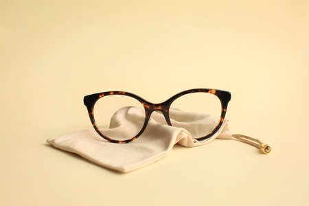 Modern fashionable acetate spectacles, torture color with textile beige bag laying on light yellow background. Фото со стока