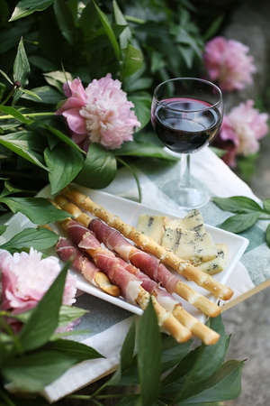 Apperitive with a glass of red wine, fresh prosciutto, grissini sticks and cheese near peony flowers in summer.