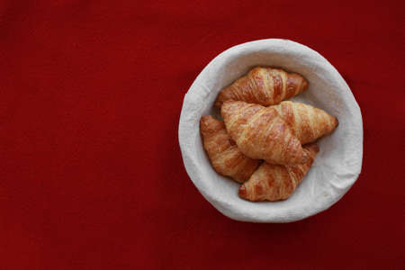 Five freshly baked tasty crusty croissants in a basket on red tablecloth .