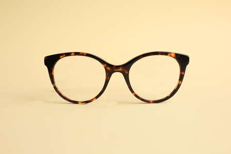 Modern fashionable acetate spectacles, torture color laying on light yellow background. 스톡 콘텐츠