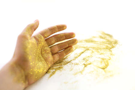 Womans hand with golden sparkles on white background. Фото со стока