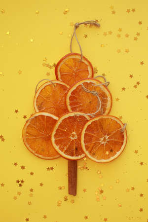 six dried orange slices with cords, imitating christmas tree with cinnamon trunk and glitter stars on yellow background