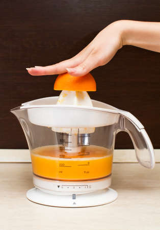 A woman squeezes orange juice photo