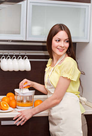 Woman is making orange juice in kitchen photo