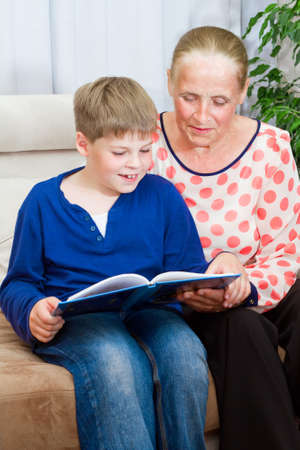 Grandmother and grandson are reading photo
