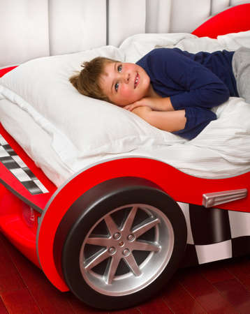 Boy dreaming in his car bed photo