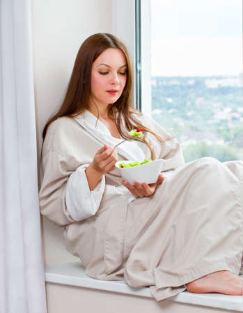 Woman eating lettuce raspberry salad at the window photo