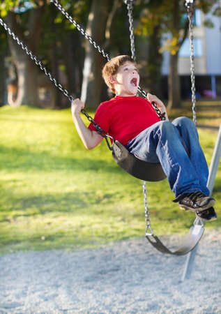 Happy young boy playing on swing in a park. Screaming and having fun. photo