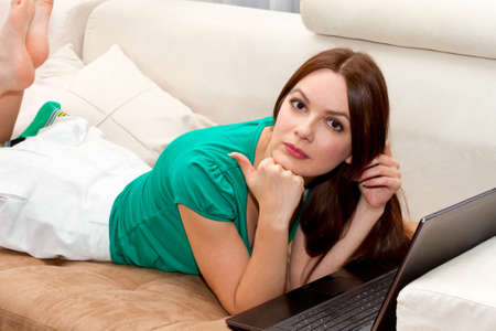 Beautiful woman lying on the sofa with laptop photo