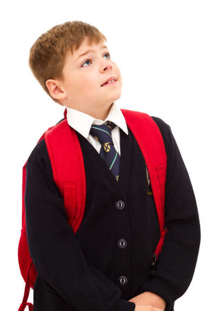 private schools: School boy standing and looking up with his backpack. Wearing in school uniform. Isolated on white.