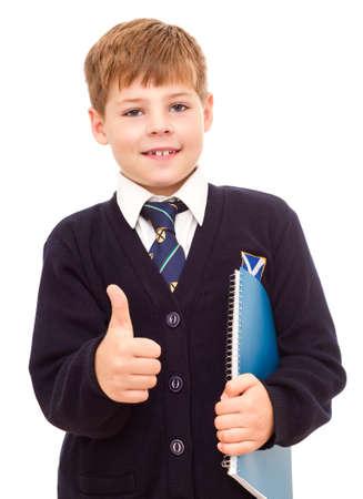 uniform school: Feliz ni�o sonriente escuela se�alando el pulgar hacia arriba signo Aceptar mano. Aislado sobre fondo blanco.