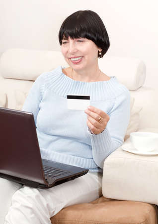 Smiling mature woman shopping online with credit card and laptop computer. Stock Photo - 15816160