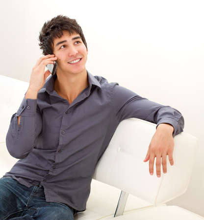 Happy smiling young man sitting on the leather sofa and talking on mobile phone. photo