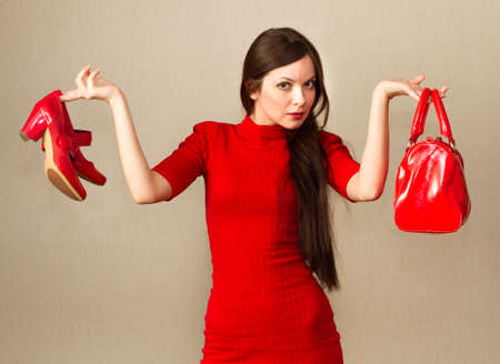 Beautiful woman in red dress holding high heel shoes and handbag in her hands  photo