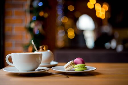 Christmas winter cappuccino coffee in white cup with colorful macaroons served on wooden table