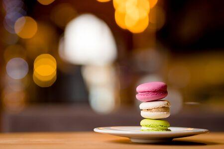 French macarons on the blured bokeh chrismas lights background.