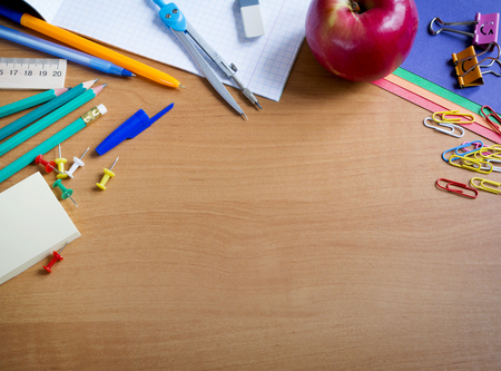 colored paper: compass, pens, notebook, colored paper, ruler, pencils, erasers, paper clips, binders, buttons laid out on wooden table